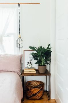 boho chic bedroom with pale pink bedding | simple rustic bedside table with a plant and books | white walls | small space bedroom with plenty of style | Get the look with a Bemz bedspread