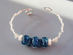 I got the Blues BANGLE Wired Bracelet, size medium, Lampwork Glass 5 Fish Designs, aqua blue teal, Joann Hayssen SRA $60.00