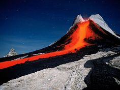 Mount Ol Doinyo Lengai in Tanzania's Rift Valley. A camera's long nighttime exposure reveals the red glow of lava, which appears brown to the naked eye.