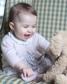 Princess Charlotte appears to be laughing as she grabs her foot and stares at a stuffed dog. This photo was also taken by The Duchess of Cambridge at home in Norfolk earlier this month