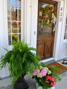 A springtime palette of pink, green and yellow is paired with a brown wood and glass door on a home built in 1820 in historic Madison, Ga. The plants, including oakleaf hydrangeas and ferns, and wreath were selected by Debbie Accetturo of Le Petit Jardin, a floral design and event planning business in Madison.