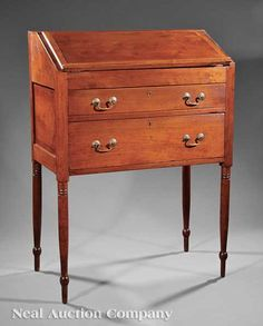 An American Federal Walnut Clerk's Desk, early 19th c., probably Tennessee or Kentucky, foldover lid opening to fitted interior, two drawers below, turned tapered legs, height 48 in., width 34 1/4 in., depth 19 1/4 in.