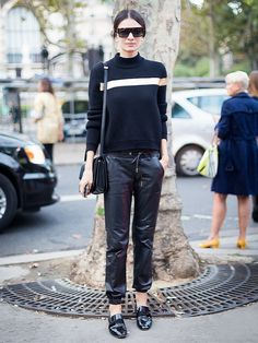 Leila Yavari wearing a black sweater with gold detail, black leather jogger pants, and black loafers
