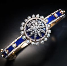 Gold bangle bracelet covered in bands of blue and white enamel, studded with pearls. The central medallion is a starburst of diamonds set on blue enamel, edged with white enamel and pearls. English c1800. 1stDibs