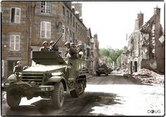 A company of M3A1 Half Tracks of the US 4th Armored Division, passing through the liberated town of Avranches, Normandy. August 1944. -