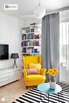 Żółty fotel wraz kolorowymi poduszkami oraz kwiatami w wazonie dominują w tym nowoczesnym, utrzymanym w stosnowanych...
