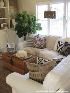 Candlescape on coffee table, basket holding magazines/ remote, white slip covered sofa Simple Details