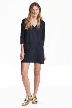 Kleid mit V-Ausschnitt : Kurzes, gerades Kleid aus festem Jersey. Modell mit 3/4-Arm, V-Ausschnitt und Vordertaschen. Halbgefüttert.