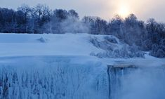 The sun rises over masses of ice at Canadian Horseshoe Falls on Thursday. Days of subzero temperatures have created a thick coating of ice and snow on every surface near the falls, including railings, trees and boulders Photograph: Aaron Lynett/AP