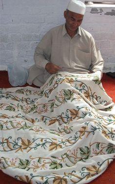 A man hand weaving embroidery on a Kashmiri shawl