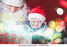 Christmas baby wearing a Santa Claus hat and Santa opening a present and gift box! Night, xmas eve, surprise. Magical light. Design. New Year