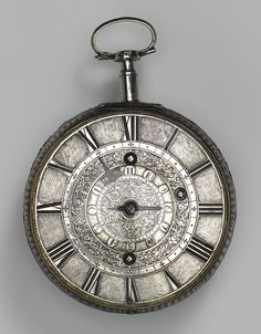 Traveling clock watch with alarm, ca. 1680  Movement by Thomas Tompion (English, 1638-1713); case by Nathaniel Delander (English, recorded 1668/69, died ca. 1691 or before 1705)  Case and dial: silver; Movement: gilded brass, steel, partly blued, and silver  Diam. of back plate 3 3/16 in. (8.1 cm)  Gift of J. Pierpont Morgan, 1917 (17.190.1512)