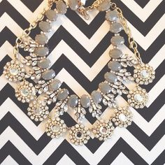 Great statement necklace, grey stones and white rhinestone work. Placed on Chevron print.