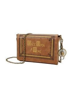 Magic is comingBrown crossbody bag from <i>Once Upon A Time with a book cover design featuring debossing detail, metallic text, brass chain link strap and clock and hook garms. Inside has zipper and pouch pockets. Hidden magnetic closure