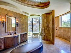 Breaking up the beige travertine tile, an upholstered oval ottoman in the middle of this southwest-style bathroom mimics the curves of the walls and ceiling. A white clawfoot tub is positioned at the center of a wall of floor-to-ceiling windows for a scenic, relaxing retreat.