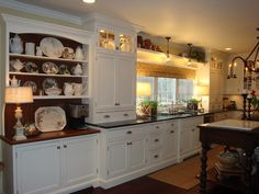This is about perfect style of cabinetry. like dish display w/ open shelves & butcher block counters at end.