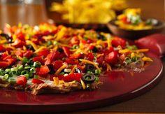 Dieser unwiderstehlich cremige Dip mit geriebenem Käse, Oliven und anderen traditionellen Taco-Zutaten hebt auf jeder Party die Stimmung!