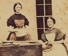 Ladies preparing food. High bodices, small collars, pushed up sleeves, aprons, no caps.