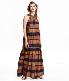 Langes, ärmelloses Kleid aus zartem Webstoff. Modell mit schmalen Trägern und kleinem Volant am Halsausschnitt. Verschluss im Nacken und breiter Volant am Saum. Ungefüttert.