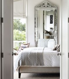 A glimpse inside this master bedroom reveals a linen-upholstered bed by Plantation, a midcentury French leather sling chair, and a Venetian cut-glass mirror from the 1920s.    Read more: Bedroom Design Ideas - Guide to Bedroom Design - Country Living