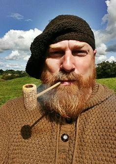 Wearin' a broon boineid whilst smokin' an American corn cob pipe.