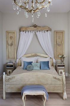 ozdony baldachim w stylu prowansalskim,drewniane stylowe łóżko z bielonego drewna,niebieskie poduszki i ozdobne panele francuskie z drewna - Lovingit.pl
