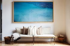 A simple collection of neutral pillows on a coordinating bench gets accented by a bright piece of oversized artwork.