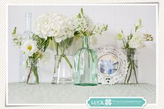 """White Flowers + Pretty Glass Bottles = Endless Possibilities ------ """"Instead of one large bouquet, I often split the flowers among bottles and jars of different sizes and heights to create a centerpiece or mantle display with more impact than a single large bouquet. I like to keep interesting glassware in convenient sizes just for this purpose."""" ~ Sarah of Luck Photography"""