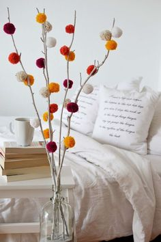 DIY pom pom tree for a pop of colour in autumn/winter. Learn how to make pompom branches as an evergreen decor addition.