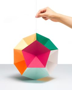 Cut colorful paper into a pentagon, fold, glue together into globe shape with string for hanging