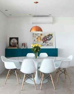 Sala de Jantar com cadeiras brancas Eames e mesa redonda branca.