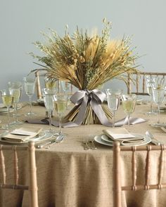 A table arrangement of grains celebrates the bounty of fall. In addition to wheat, which symbolizes a fruitful life, this textured display includes other dried grasses, so it can be made weeks ahead. The final flourish? A luxurious satin bow.