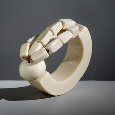 """Catherine Noll created her jewellery in Paris in the 1970s. She collaborated with many of the greatest names in fashion including Nina Ricci, Chanel, Christian Dior and Tiffany. Catherine Deneuve described the jewellery, saying """"I think it was the primitive and sophisticated form of her jewellery that seduced me."""" Noll worked primarily in wood, ivory, perspex and crystal. """"The jewellery is unusual, bold and elegant."""" says Harry Fane."""