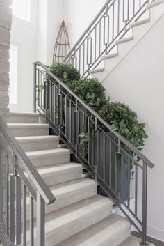 Neutral staircase with gray metal railings via Omaha Street of Dreams. Image via…