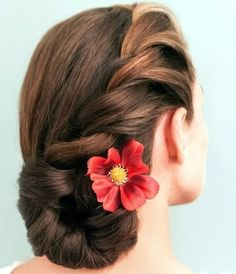 You can easily achieve this look starting with curled hair. Brush out the curls and side part your strands. Use a styling product and run it through your locks with your fingers to keep things smooth. Then, rope braid your hair along one side and twist the bottom into a bun.