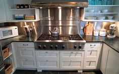 Chef's kitchen with professional appliances, white cabinets, open shelving, honed marble countertops.