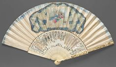 "1730-1740, Europe - Fan - Skin leaf etched and painted in gouache; pierced, carved, and gilded sticks backed with mother-of-pearl; paste - Reverse: picture of couple seated surrounded by printed ""lace"" on blue stylized background, gilt border, in center of leaf; blue shading along top, narrow gilt band at bottom"
