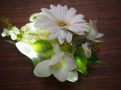 Glow in the dark custom prom corsage that lights up with an on/off switch in shades of white, green and yellow with diamonds, glitter, moss, lily of the valley, gerber daisy, freesia, and bells of Ireland on silver cuff with matching boutonnière. www.urbanelementsinteriorspace.com in Portland, OR.