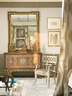 In the Master Bedroom, Windsor Smith consummates a marriage of cultures integrating Eastern, Indian and African elements. Bathed in light streaming in from windows on two sides, Smith's furnishing choices balance strong contemporary forms with the ornate and the decorative. Opalescent, embroidered silk lines the bed's canopy, supported by a nail-studded zebra hide frame. Upholstered wall panels contrast with green-gray walls   - Veranda.com