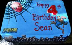 Spiderman 4th Birthday Cake. Blue buttercream iced, sheet cake decorated with spiderman spinning his web over the city.