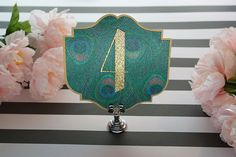 Add glamour to your table number cards with a peacock print Art Deco design.