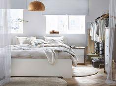 Ein helles Schlafzimmer mit einem großen ASKVOLL Bettgestell in Weiß, NATTLJUS Bettwäsche-Set in Beige und langflorigen ÅDUM…