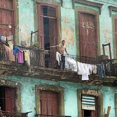 A man looks out over a balcony from a house in Cuba where Cuban officials plan to let Cubans buy and sell their own homes for the first time in 50 years