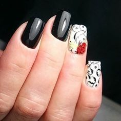 \Beautiful black and white rose nail art design. The nails are painted with black and white background and painting additional designs on top I alternating colors. The lone red rose on the nails looks absolutely stunning.