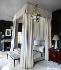 Custom black paint by Fine Paints of Europe sets off a magnificent bed in the master bedroom. The voluminous canopy and hangings are in Corelli cotton from Fabricut with Scalamandré tape trim, and the bed frame is upholstered in Lockett from Stark. Pendant lanterns, Circa Lighting.   - HouseBeautiful.com