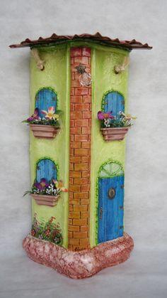Telha decorada - Cumieira Grande - técnicas: pintura à óleo, modelagem em massa epox (tijolos e telhado), porta e janelas em palitos de sorvete, flores de plástico e seda, marmorizado, peças de bijuteria. Alça em macrame