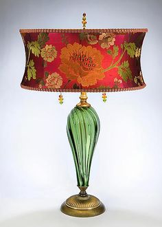 Mixed media table lamp that is just superb. Green blown glass green and salmon flowered shade and beaded pulls and filial.