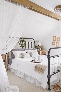 For softness in this couple's Indiana bedroom, lace curtains hang on either side of the iron bed.