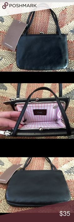Nest Black Leather Two Handle Wristlet NWT This is a nest black two handle leather wristlet. Center kiss lock compartment with two zippered compartments. Lined in pink and white stripe fabric. Measures 5 1/2 inches long by 4 inches high by 2 inches deep. No trades please! Nest Bags Clutches & Wristlets