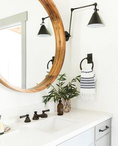 Wood framed round mirror farm sink with dark faucet, striped bathroom hand towel. Boho feel